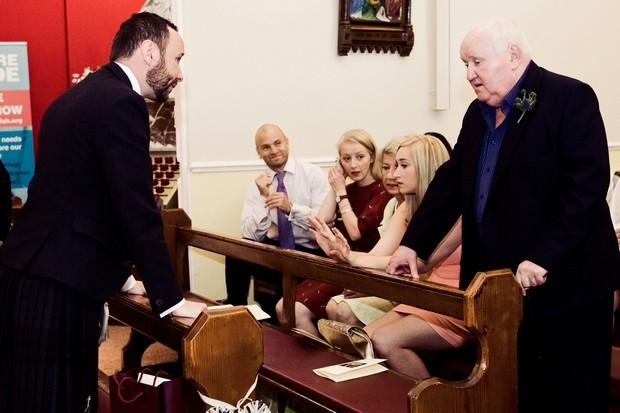 groom talking to guests in church