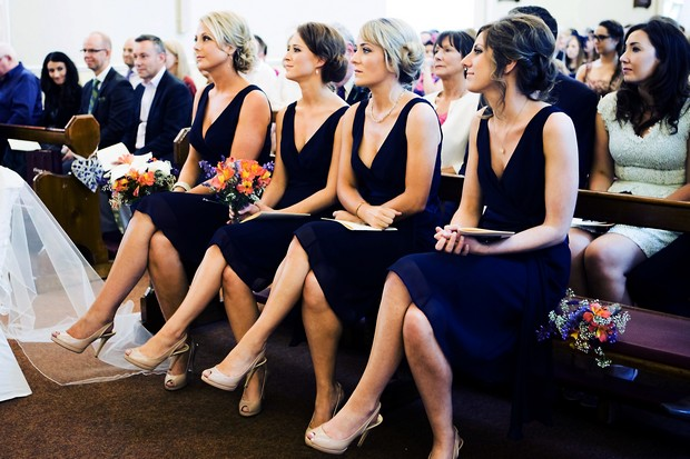 bridesmaids in short navy dresses in church