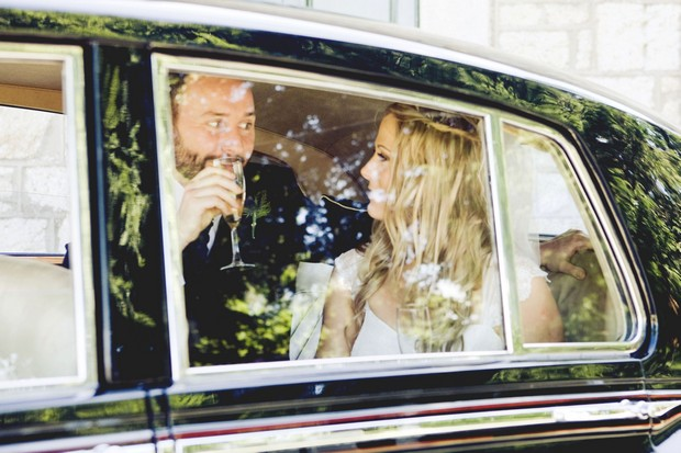 bride and groom in wedding car with Champagne