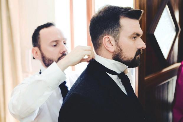 Groomsman fixing groom's tie