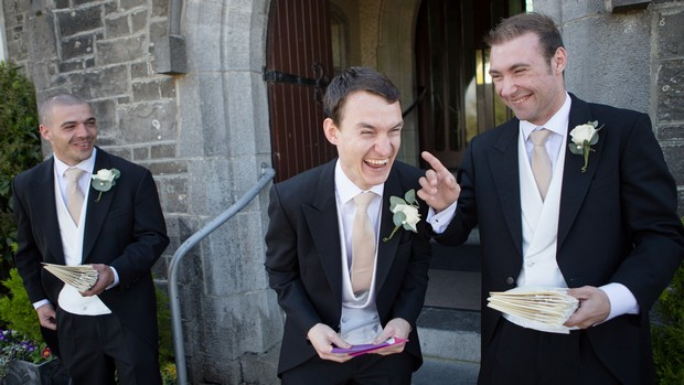 groom and groomsmen laughing outside church