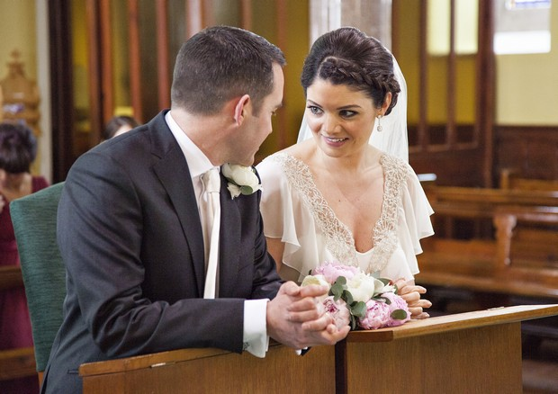 bride and groom chatting in church