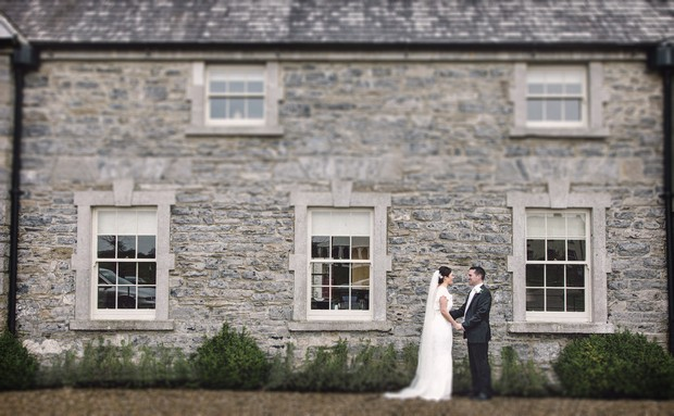 bride and groom in front of stone wall