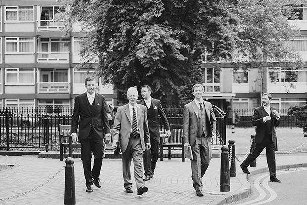 black and white groomsmen walking to venue