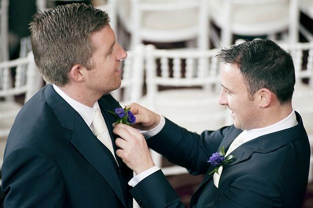 groomsmen pinning button hole on groom