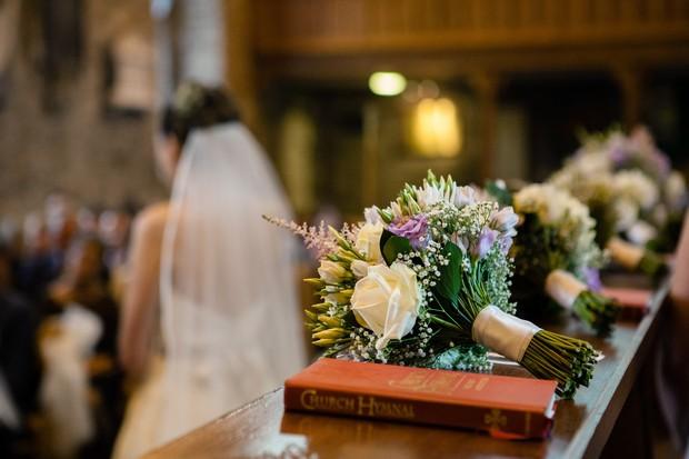 bridesmaids wedding bouquets on church bench