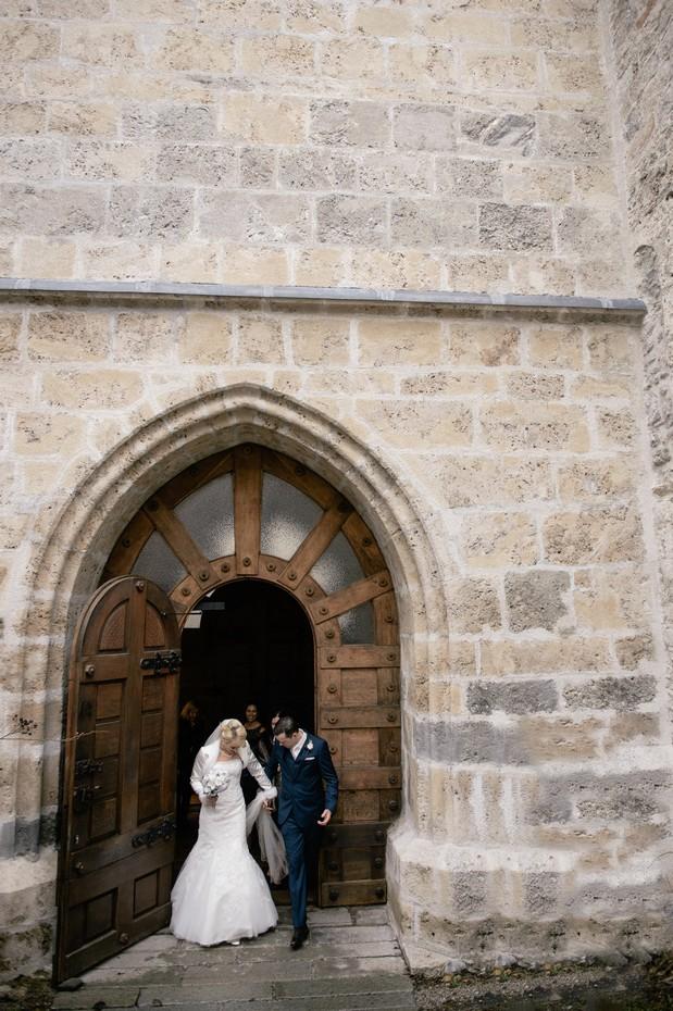 bride groom against exposed brick church