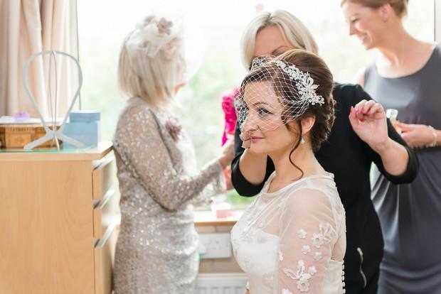 11-bride-fixing-wedding-birdcage-veil