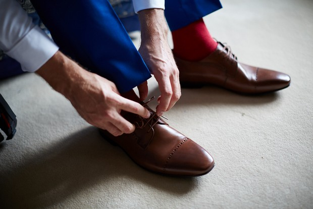 Groom tying laces to brown shoes
