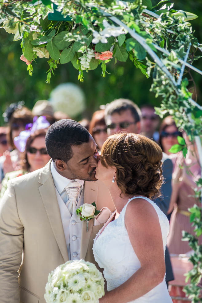 bride groom kissing garden wedding ceremony