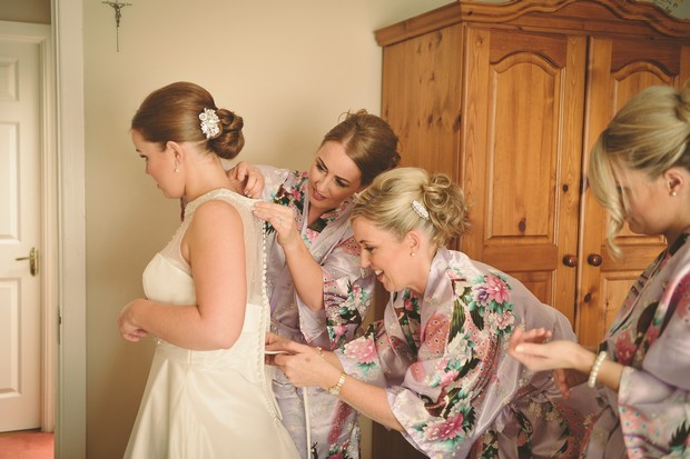 bridesmaid-dressing-bride-morning-wedding