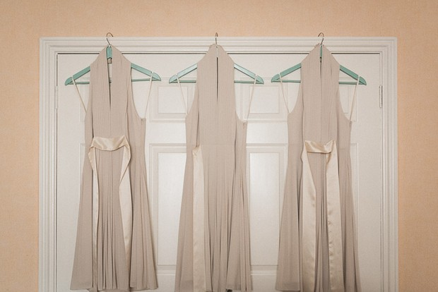 nude-bridesmaids-dresses-hanging-beige-background