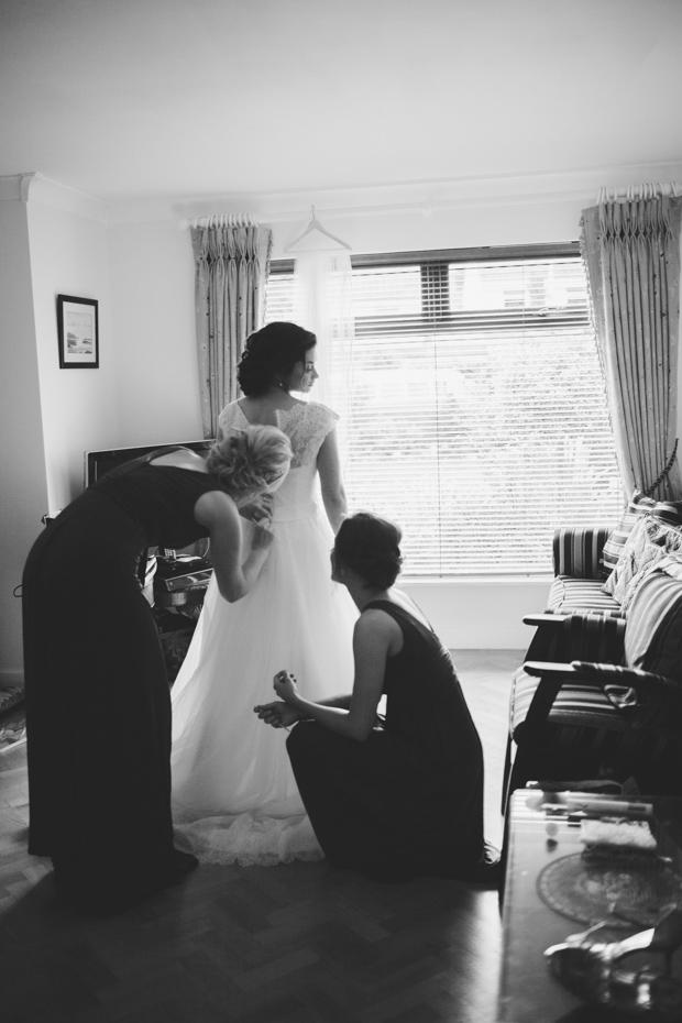 17_bridesmaids_fixing_brides_wedding_Dress