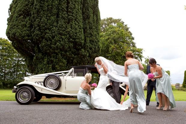 2-bridesmaid-fixing-wedding-dress-wind-weather