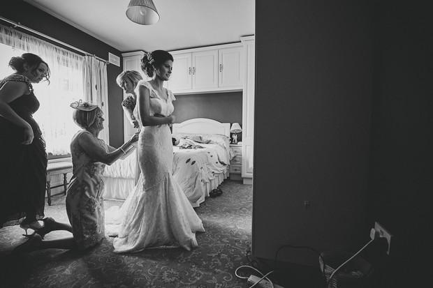 15-Bridesmaids-halping-bride-into-wedding-dress