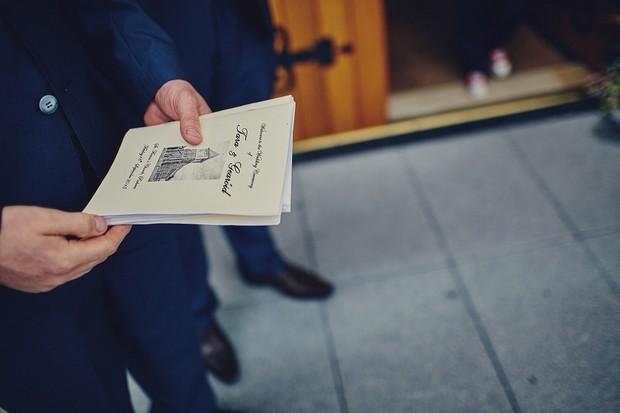 22-Groomsman-holding-wedding-mass-booklet-church-ceremony