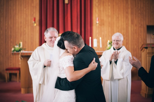 bride-and-groom-hugging-church-wedding-ceremony