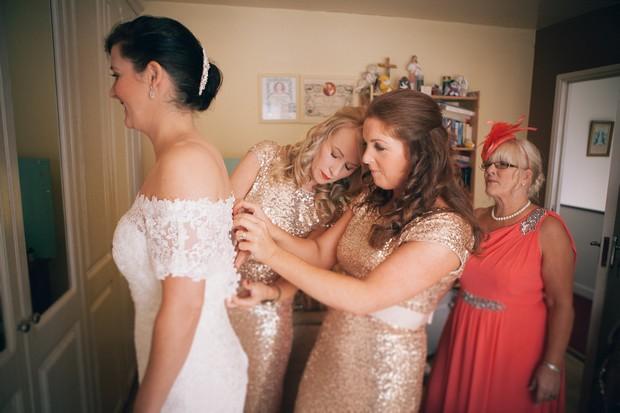 bridesmaid-buttoning-up-bride's-dress-wedding-morning