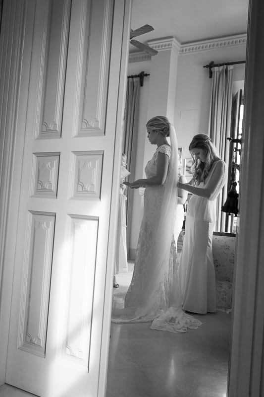 7-bridesmaid-helping-bride-getting-ready-dress-fitting-Owen-Farrell-Photography