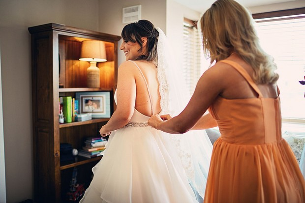 15-bride-getting-ready-dress-fitting-bridesmaid-weddingsonline