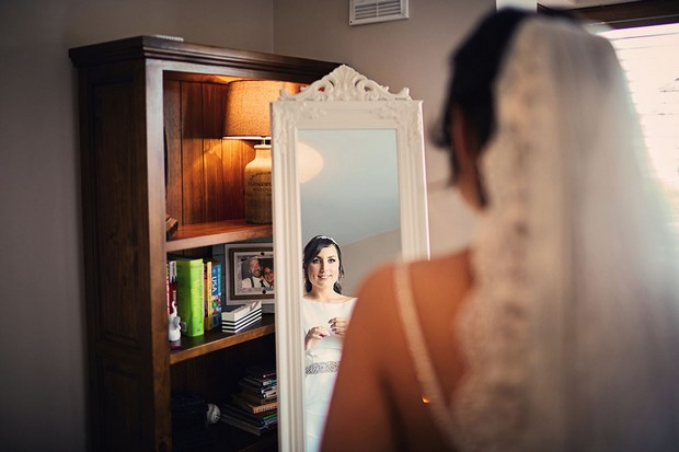 16-bride-looking-mirror-getting-ready-wedding-morning-weddingsonline