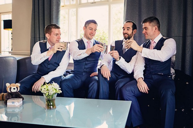 3-Groomsmen-getting-ready-drinking-cheers-Fleeting-Moments