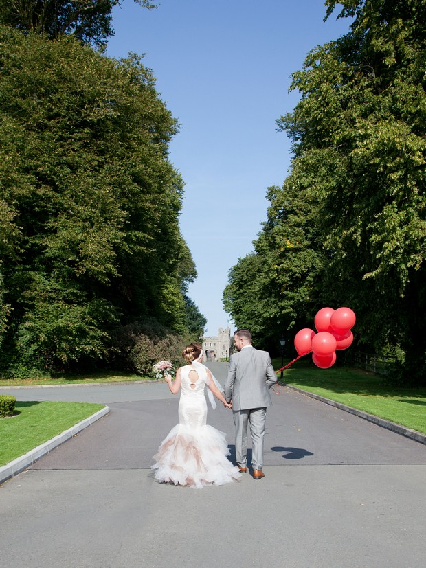 bellingham-castle-real-wedding-bride-and-groom-with-red-balloons