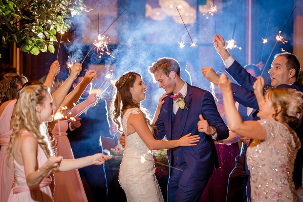bride-and-groom-surrounded-by-guests-with-sparklers