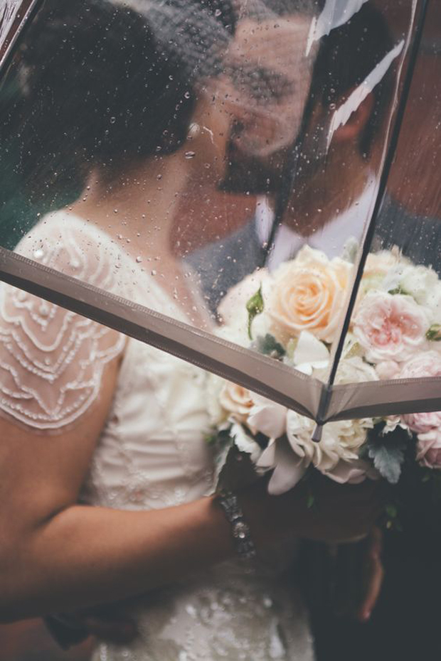 couple-kiss-under-umbrella-wedding-day