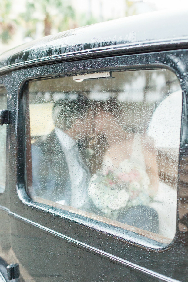 couple-kissing-inside-car-rain-day-wedding-photos