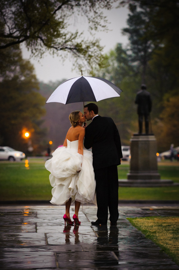 couple-kissing-under-umbrella-wedding