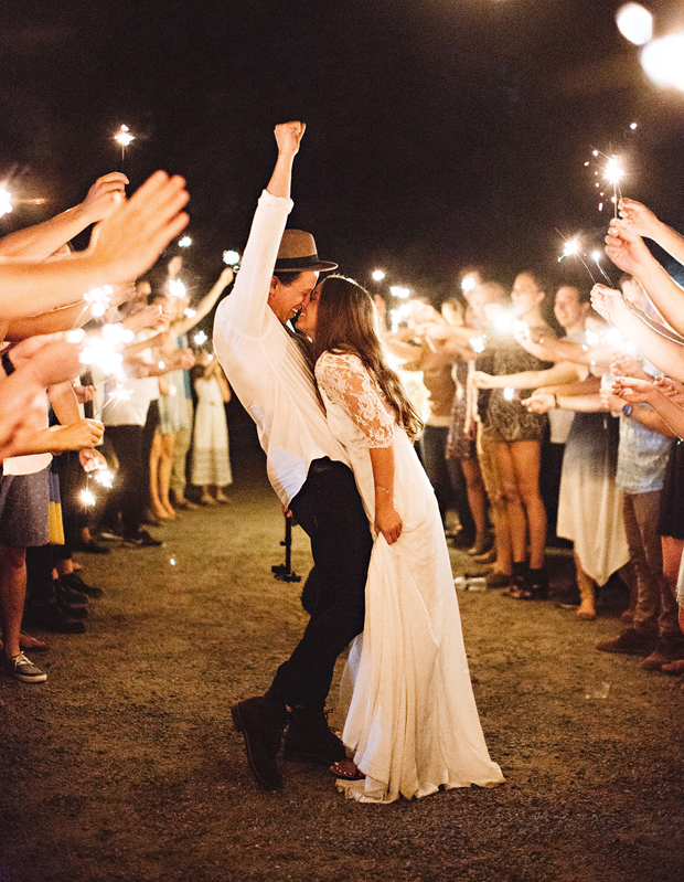 couple-surrounded-by-friends-with-sparklers-wedding