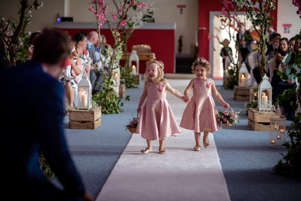 flower-girls-in-pink-dresses-walking-up-the-aisle