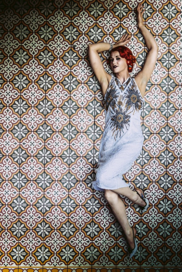 Model lying on ground, vintage flapper dress, red hair, 20s.