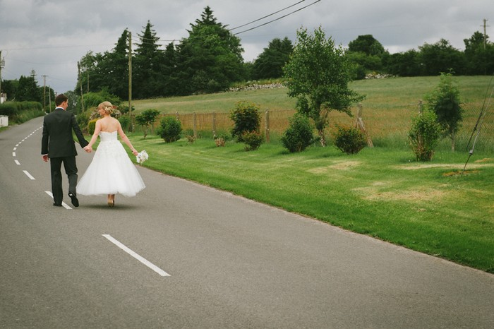 bride and groom walking down a road together